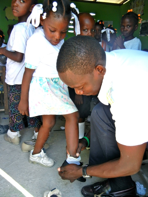 the boss himself fitting shoes on the kids